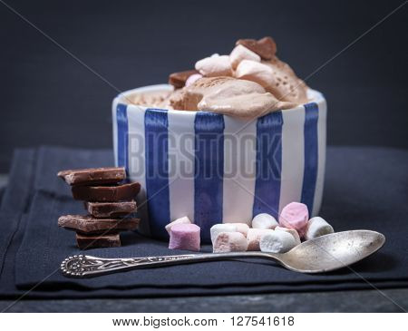 Homemade vanilla and chocolate ice cream with marshmallow, served in ceramic bowl on dark background.