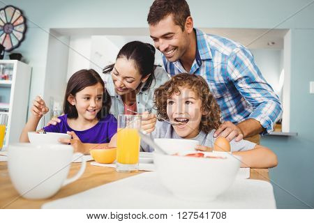 Cheerful man and woman with children during breakfast at home