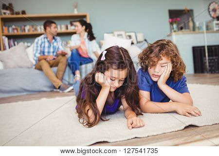 Close-up of children resting on carpet while parents sitting in background at home
