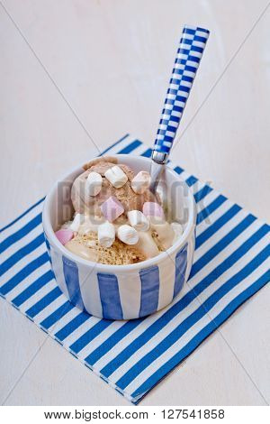 Homemade vanilla and chocolate ice cream with marshmallow, served in ceramic bowl on white wooden background.