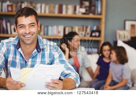Portrait of happy man with documents while family sitting in background at home
