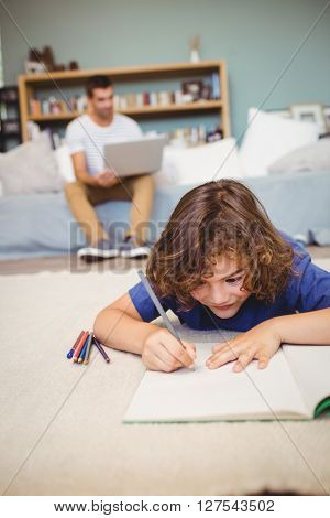 Close-up of boy writing in book while father working in background