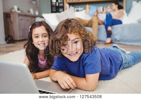 Close-up portrait of siblings lying by laptop on carpet at home