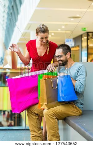 Couple in shopping mall with bags sitting for rest