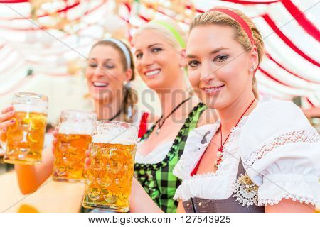 Friends drinking together Bavarian beer in national costume or Dirndl on Oktoberfest