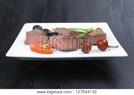 meat savory : grilled beef fillet mignon served on white plate over black wooden table with chili pepper and tomatoes