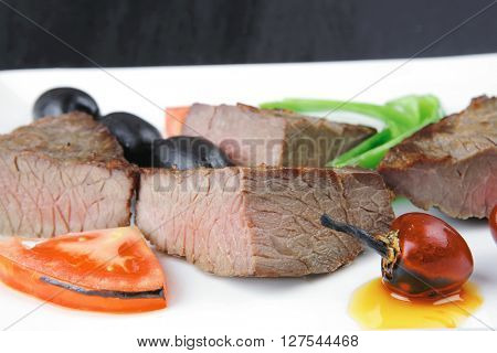meat savory : grilled beef fillet mignon served on white plate over black wooden table with chili pepper and tomatoes . shallow dof