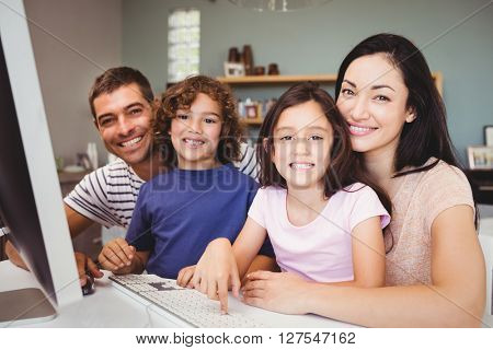 Close-up portrait of happy family sitting by computer at home
