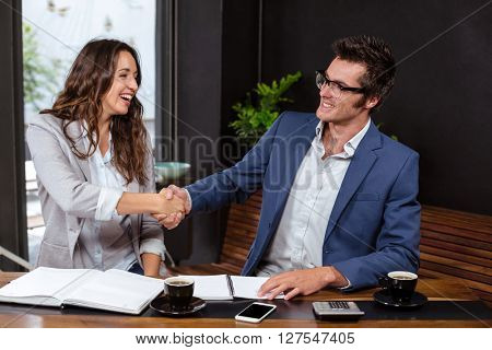 People giving handshake in a cafe