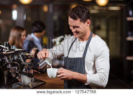Smiling barista preparing cappuccino in the bar