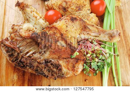 meat : grilled quarter chicken garnished with green sprouts and red peppers on wooden plate isolated over white background
