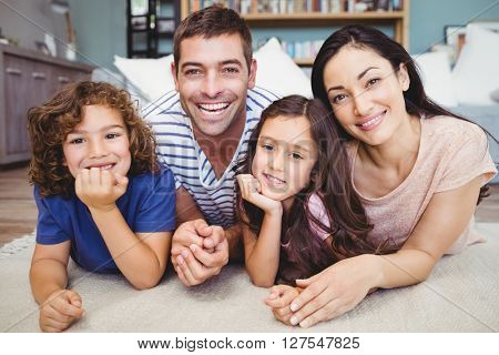 Close-up portrait of cheerful family lying on carpet at home