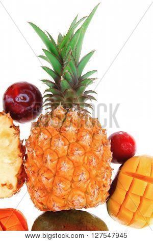 exotic fruit food - a lot of fresh raw tropical fruits include pineapple mango and red plums isolated over white background