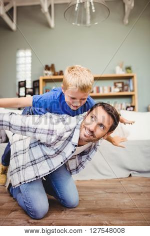 Happy father playing with son on hardwood floor at home