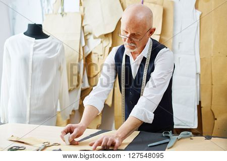 Mature tailor with chalk outlining paper pattern