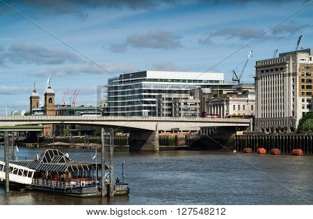 London UK - May 4th 2015: photo of 70's-style buildings near the City of London with a red English bus going over a bridge.