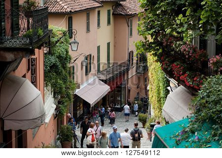 Bellagio, Italy - September 2nd 2015: tourists walking up and down the narrow hilly paths of Bellagio one of most popular tourist locations near Lake Como Italy.