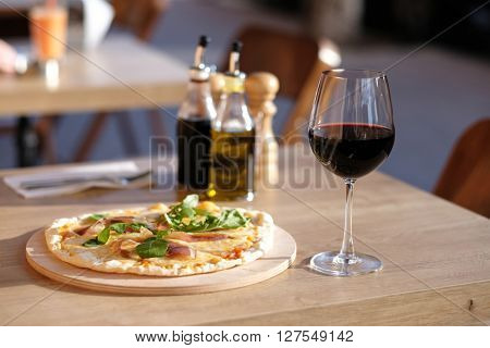 Pizza and glass of red wine in outdoor restaurant