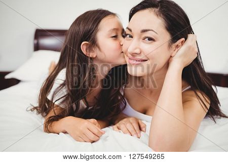 Close-up of cute daughter kissing mother on bed at home