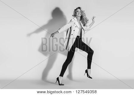 The emotional fashion-model running in black leggings on a white background. Studio shot.