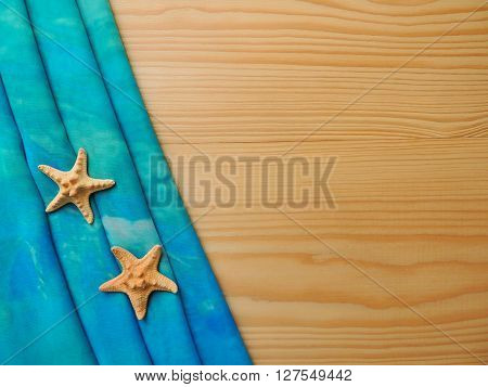 Folded pleats turquoise pareo with sea stars on wooden background.
