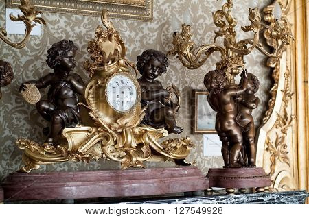 Varenna, Italy - September 4th 2015: closeup of the golden angel-decorated French clock inside the Music Room at Villa Monastero a house museum near Lake Como in Varenna Italy.