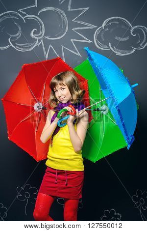 Joyful teen girl in colorful clothes stands under bright umbrellas. Summer inspiration.