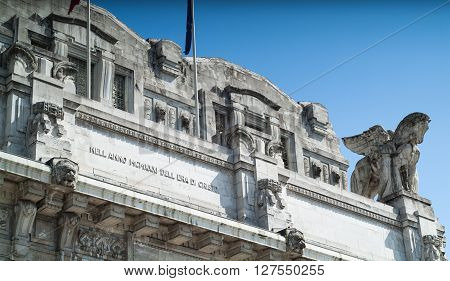 Milan, Italy - September 5th 2015: closeup photo of the facade of the Milano Centrale railway station against blue sky. The writing in Italian reads