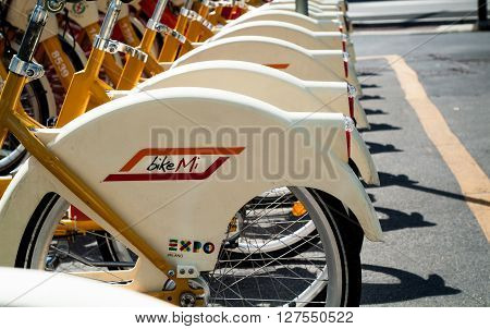 Milan, Italy - September 5th 2015: closeup photo of yellow and white hire bicycles in Milan Italy.