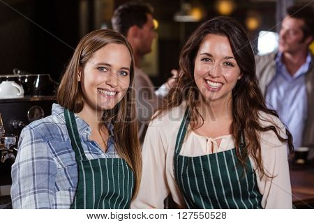 Pretty baristas smiling at the camera in the bar