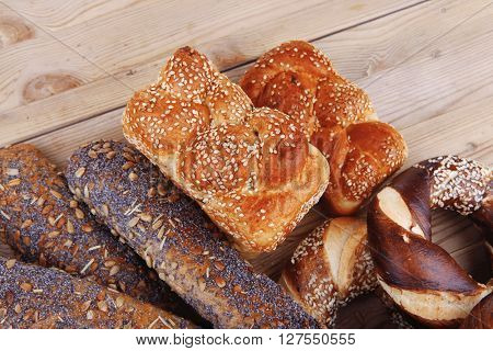 fresh mix of baguettes , pretzels and wheat bread, on wooden table