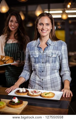Smiling woman standing in the bar and looking at the camera