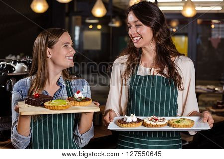 Pretty baristas holding desserts in the bar