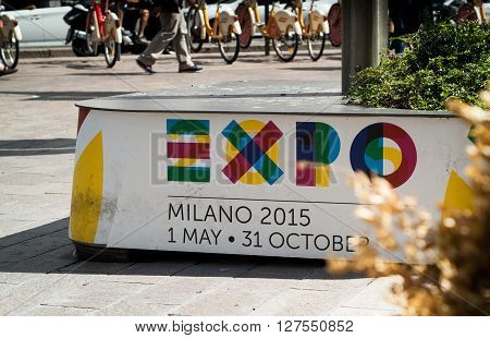 Milan, Italy - September 5th 2015: pedestrians walking past a white bench advertizing the 2015 Expo in Milan.