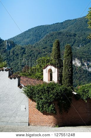 a small bell tower photographed against cypress trees and mountains in Abbadia Lariana Italy