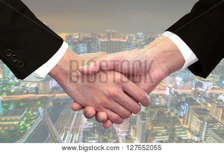 Business handshake over cityscape