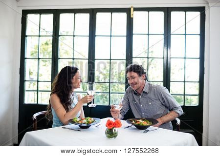 Couple holding wine glass and interacting at dining table in the restaurant
