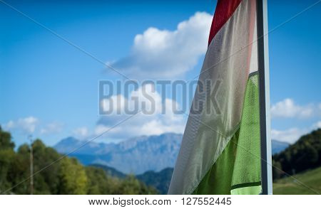 closeup photo of a wind-blown Italian flag with Piani d'Erna (part of the Alps) in the background