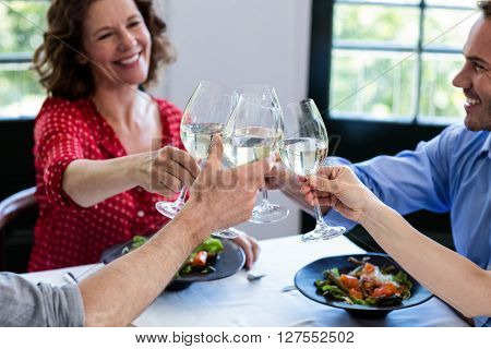 Happy friends toasting wine glass while having lunch in restaurant