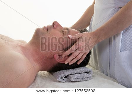 Cranial osteopathy therapy in a medical room hands of femal