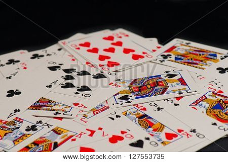 Playing cards scattered randomly on a black background.