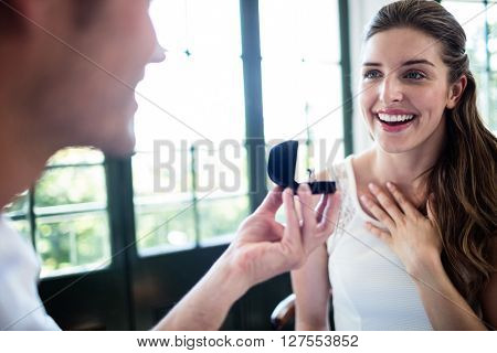 Man proposing to woman offering engagement ring in a restaurant