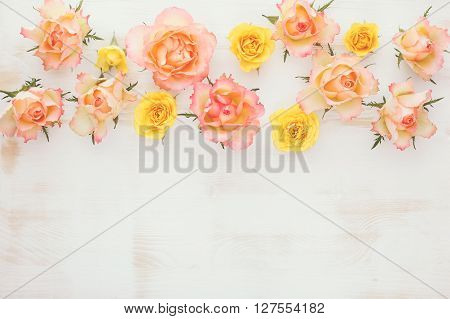 Assorted roses heads with dew.  Natural rose flowers  in a border on a rustic wood background. Top view, vintage toned image, blank space