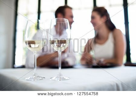 Close up of two wine glasses and couple in background on a date in a restaurant