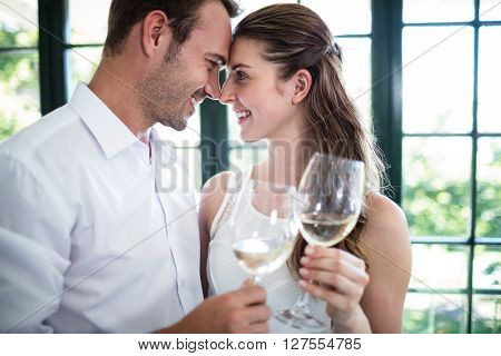 Couple looking face to face and toasting wine glasses in a restaurant