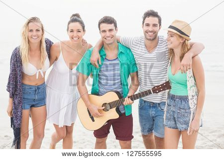 Group of friends standing on the beach with a guitar and looking at camera