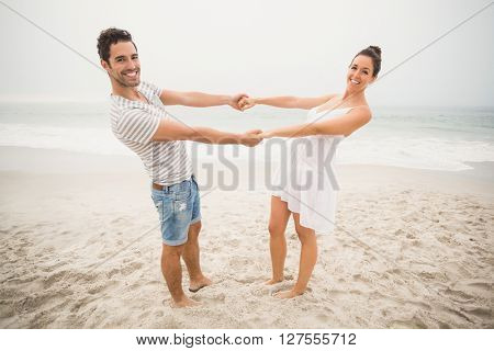 Happy couple holding hands and bending backwards on the beach