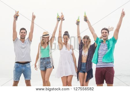 Group of happy friends holding beer bottle