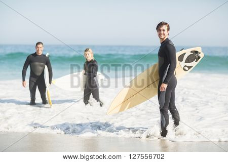 Portrait of surfer friends with surfboard standing on the beach on a sunny day