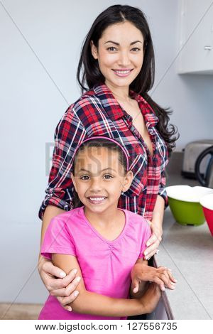 Portrait of happy young woman standing with her daughter in kitchen